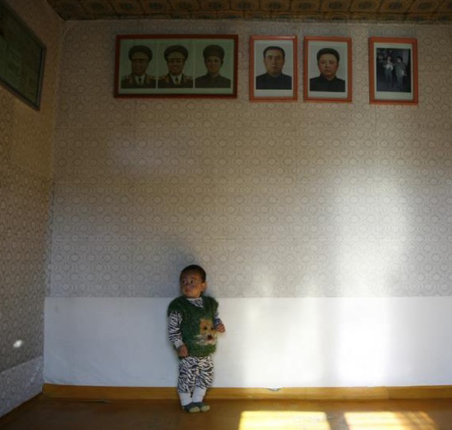 toddler in room with portraits of the leaders high up on the wall